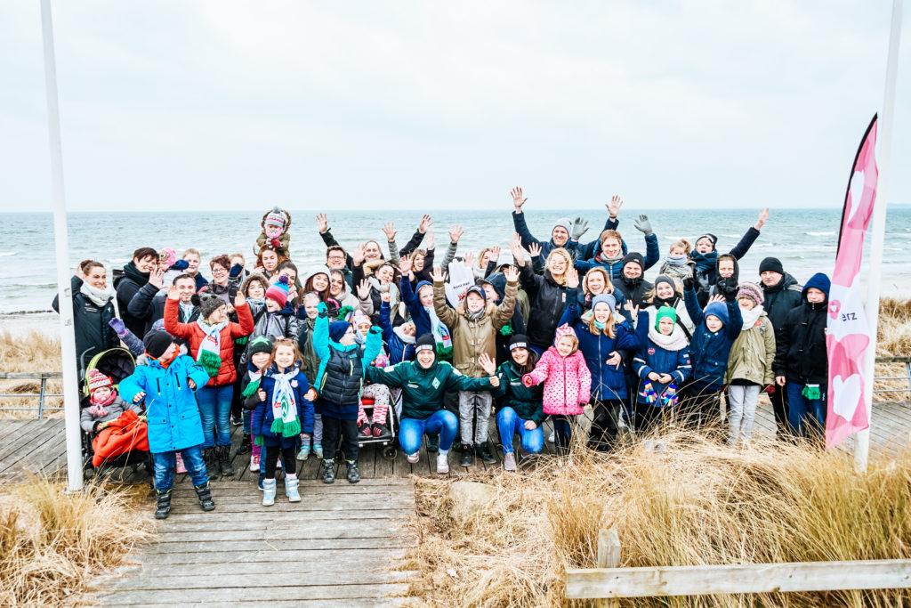 """10 Familien winkend am Strand an der Ostee. Den 10 Familien wurde bei dem Projekt """"Ferien mit Herz"""" der Osterurlaub spendiert."""
