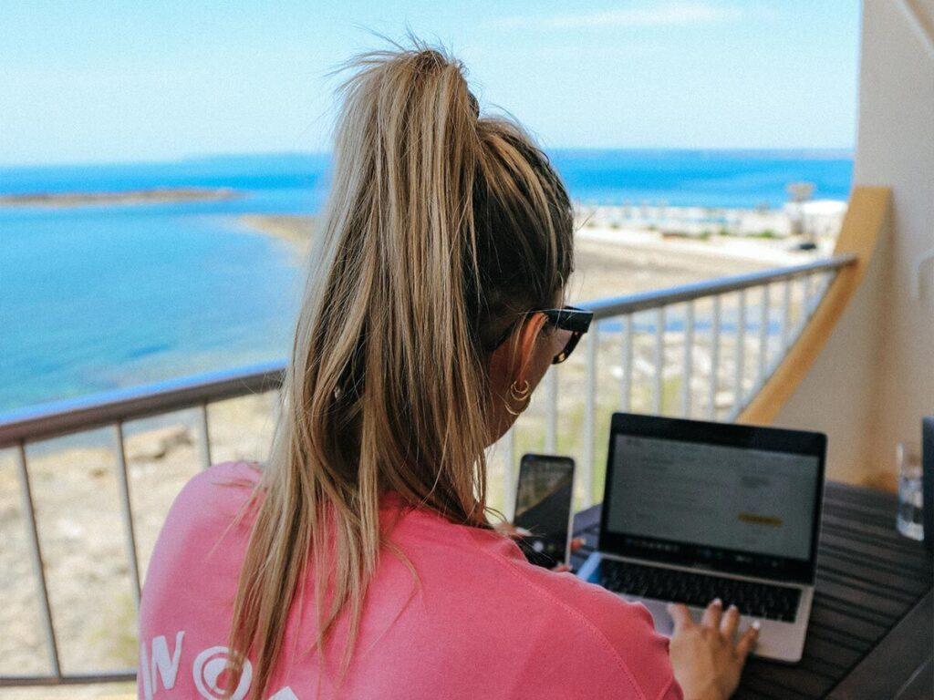 Mitarbeiterin mit Handy und Laptop auf einem Balkon mit Meerblick