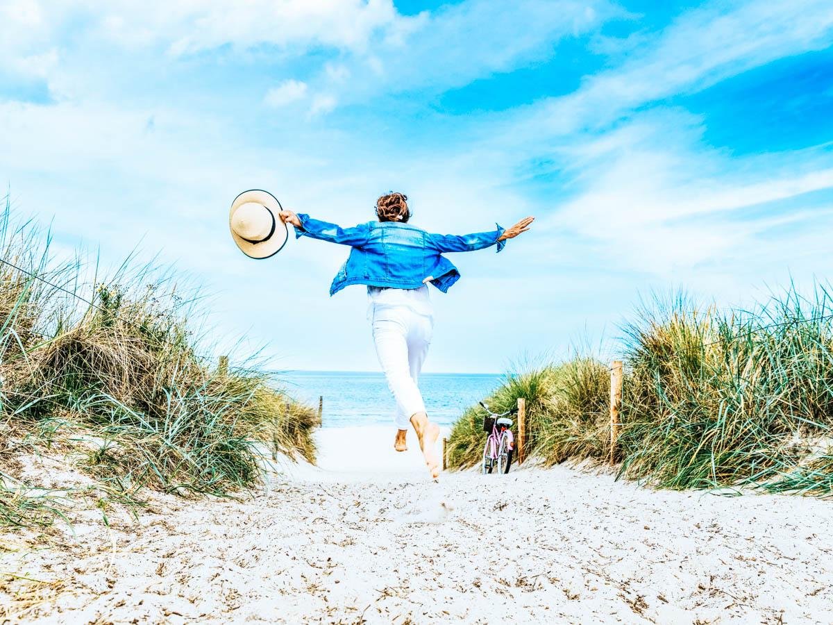 Frau hält einen Sonnenhut und läuft zwischen Dünen zum Strand hinunter, im Hintergrund sieht man das Meer